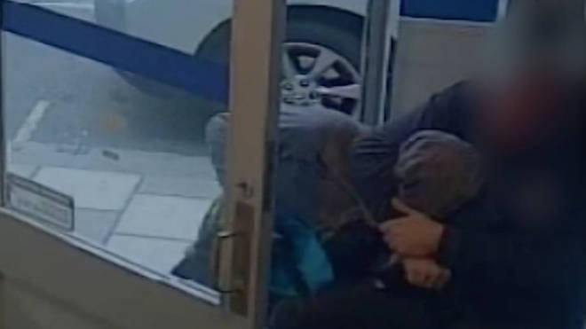 Hero gets bank robber in a headlock