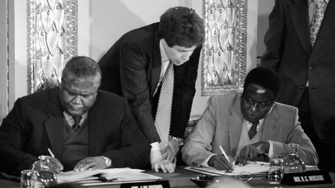 Guerrilla leaders Joshua Nkomo (L) and Robert Mugabe (R) signing the Rhodesia ceasefire agreement