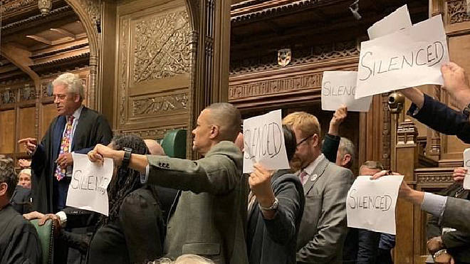 Opposition MPs hold up protest signs in Parliament