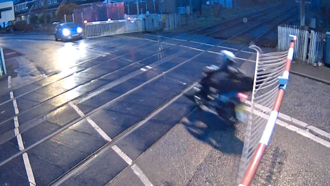 Moped riders risk their lives by speeding through a level crossing.