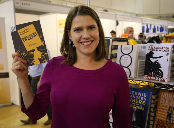 Jo Swinson holds a signed copy of her party's special edition manifesto during a tour of exhibition stands at the Liberal Democrats autumn conference at the Bournemouth International Centre in Bournemouth.