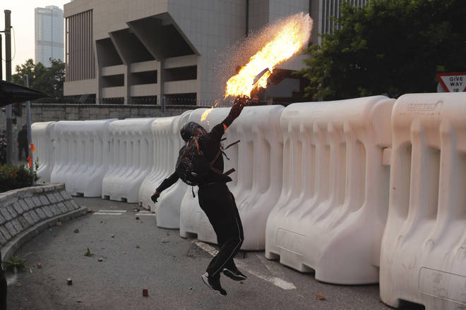 An anti-government protester throws a Molotov cocktail during a demonstration near Central Government Complex in Hong Kong.