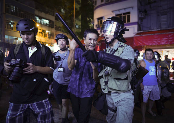 A Pro-China supporter is escorted by police after confronting journalists in Hong Kong.