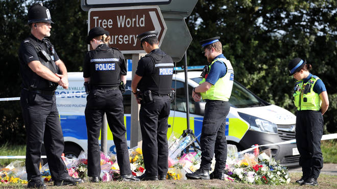 Officers pay their respect to their colleague at the scene of the crime in Berkshire