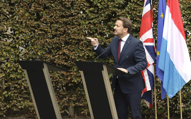 Luxembourg's Prime Minister Xavier Bettel, right, addresses a media conference next to an empty lectern intended for British Prime Minister Boris Johnson.