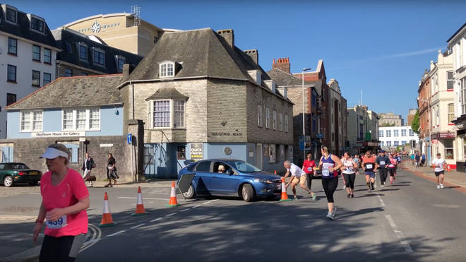 A man battles with the driver to stop her driving onto the marathon route