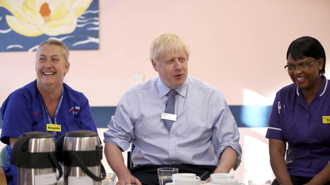 Prime Minister Boris Johnson meets members of staff during a visit to Whipps Cross University Hospital in Leytonstone, east London,