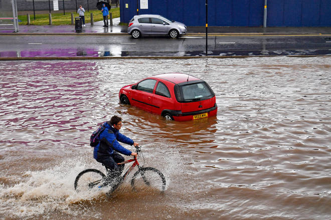 A man cycles past a stranded car on a flooded road in Birmingham city centre.