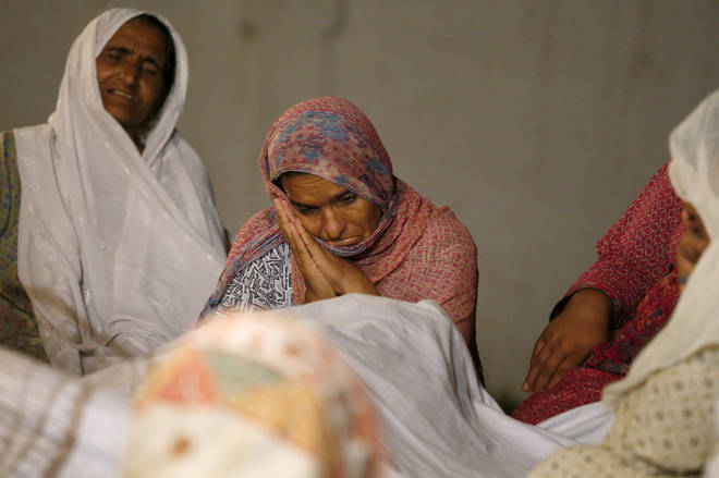 Women mourn beside the dead body of their family member who died in the earthquake