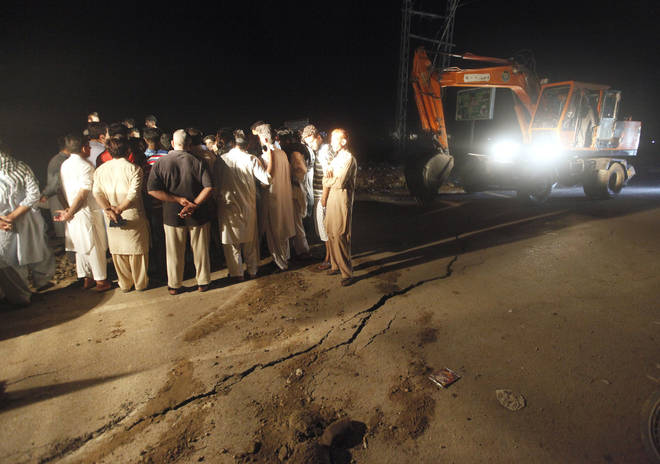 People gather next to cracks on a road caused by a powerful earthquake in Jatlan near Mirpur, in northeast Pakistan