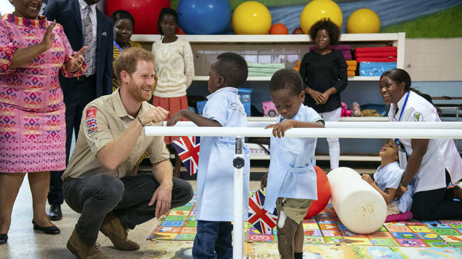 Prince Harry meets Barnaby Jose Mar, 6, as he visits the Princess Diana Orthopaedic Centre in Huambo, Angola