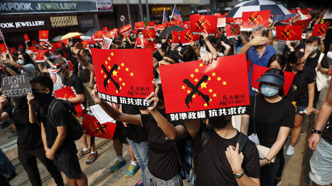 Protesters hold up anti-Chinese Government signs