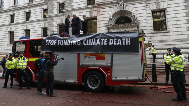Extinction Rebellion climate activists stand on a fire engine outside the Treasury building in London after activists sprayed hundreds of litres of fake blood on the building