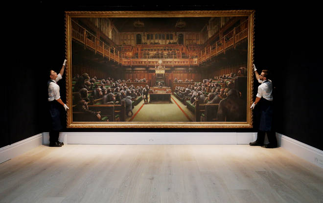 Sotheby's gallery assistants handling Banksy's Devolved Parliament painting