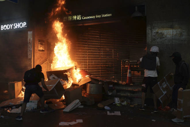Protesters set cardboard boxes on fire at the entrance to the Causeway Bay Subway station in Hong Kong