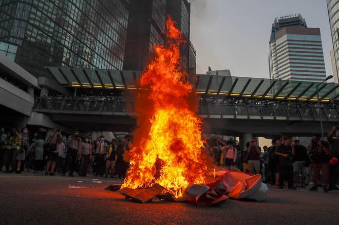 Protesters burn a China 70th anniversary celebration banner in Hong Kong