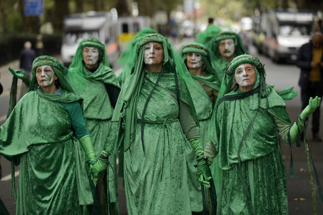 Green costumed Extinction Rebellion climate change demonstrators walk together in silent protest on Millbank in London.