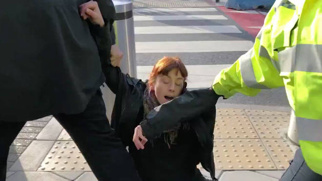 An Extinction Rebellion protester is being dragged away by police