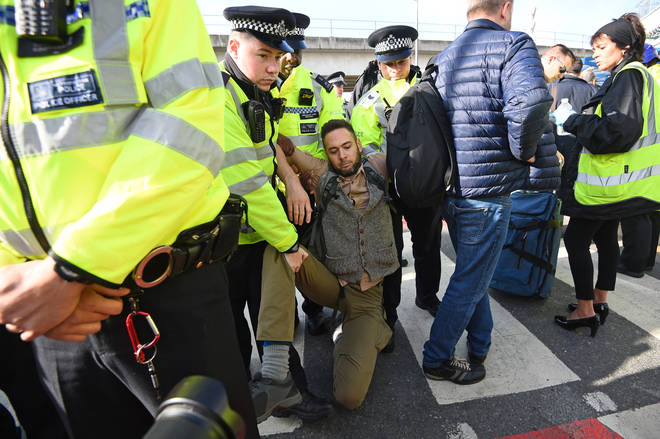 A man is removed by police officers after activists tried to block City Airport