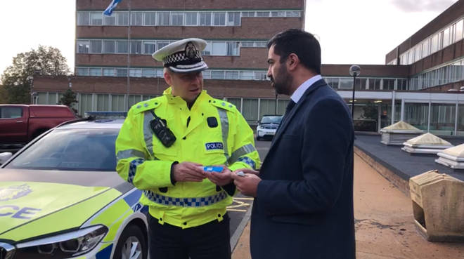 Justice Secretary Humza Yousaf examining a mouth piece with Ch Supt Stewart Carle