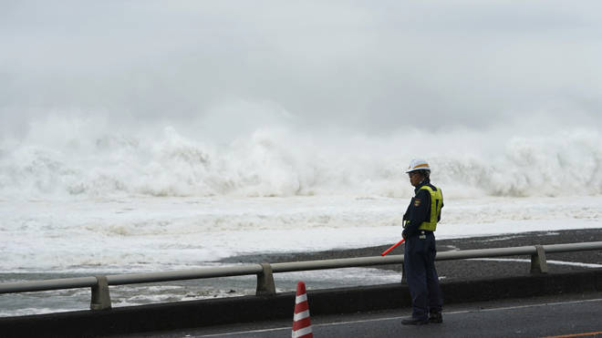 An official looks on at high seas caused by the typhoon