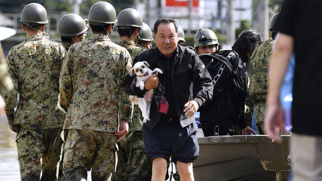 Troops walks past as a man rescues his dog in Motomiya, Fukushima prefecture