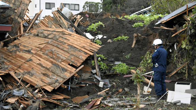 A police officer looks at a house damaged by Typhoon Hagibis, in Tomioka