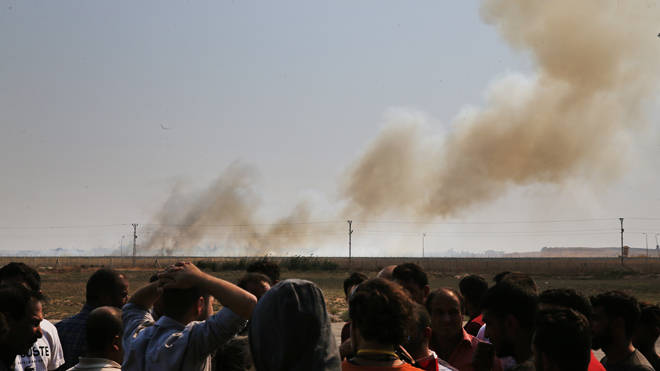 Smoke billows from fires on targets in Tel Abyad, Syria, caused by bombardment by Turkish forces
