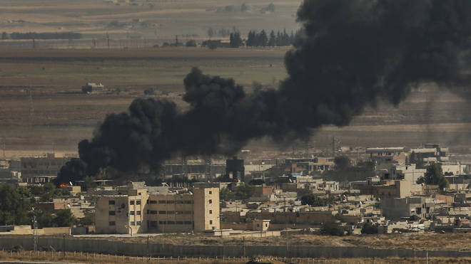 Smoke billows from fires on targets in Ras al-Ayn, Syria, caused by bombardment by Turkish forces