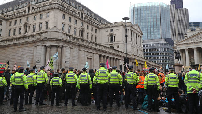 Police attempt to push back protesters as they continue to block the road outside Mansion House