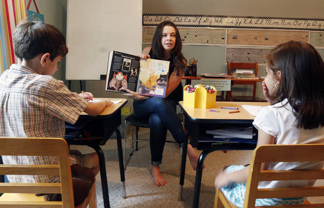 A homeschooling mom reads to her children at home