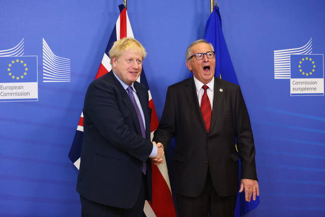 Boris Johnson and European Commission President Jean-Claude Juncker shake hands as they meet the press during an EU summit in Brussels