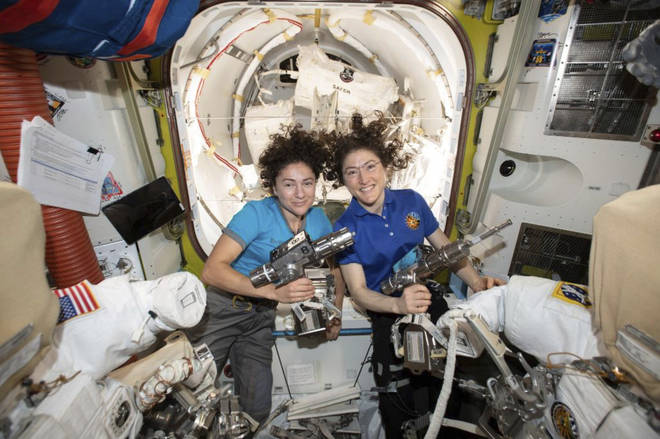 Astronauts Jessica Meir, left, and Christina Koch pose for a photo in the International Space Station