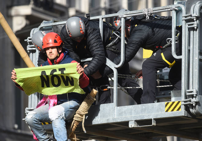 Police attempt to remove a protester that is sat on top of a bamboo structure built to block the road at Oxford Circus