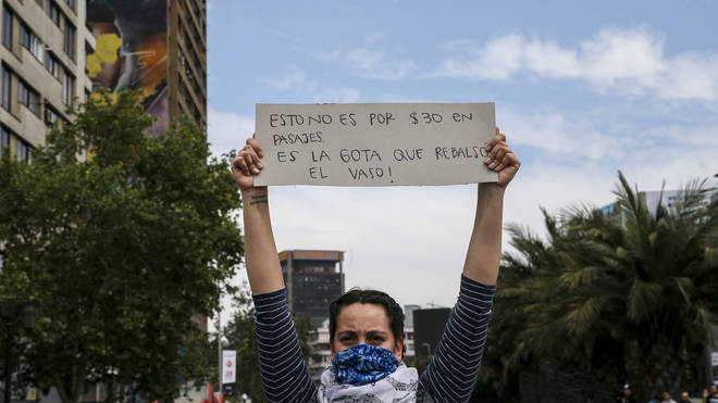 "A demonstrator raises a sign that reads in Spanish ""This is not for 30 pesos in fare, it&squot;s the drop that overflows the glass"""