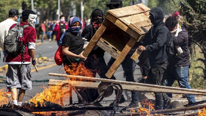 Demonstrators build a burning barricade during a protest in Santiago, Chile