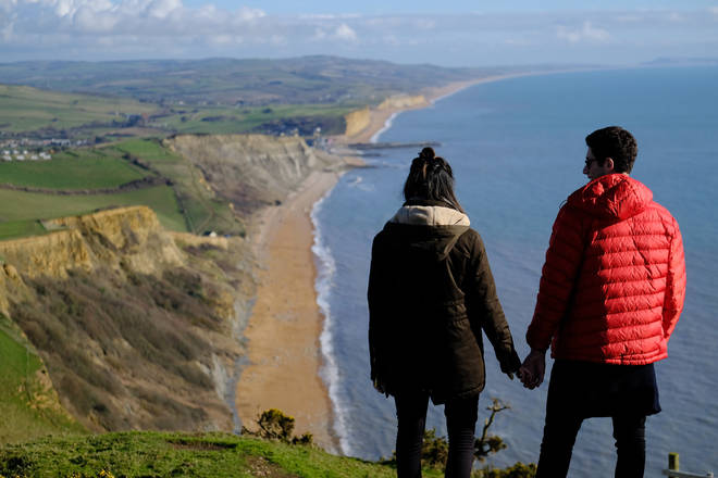 People admire the view towards West Bay from the South West Coast Path near Bridport, Dorset