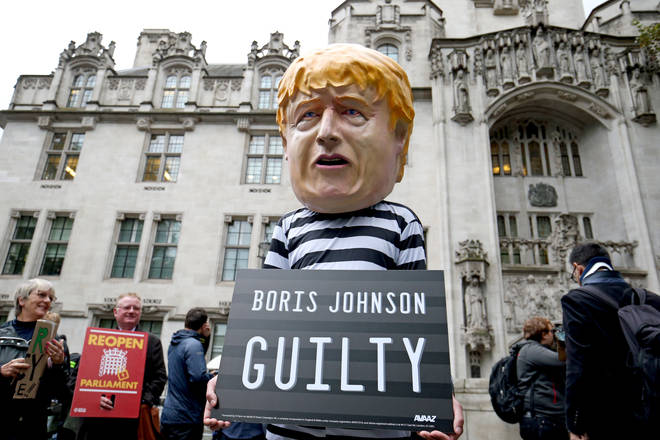 A man wearing a giant Boris Johnson mask and prison clothing