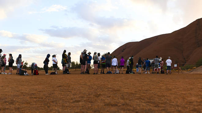 Tourists come from all over the world to climb Uluru