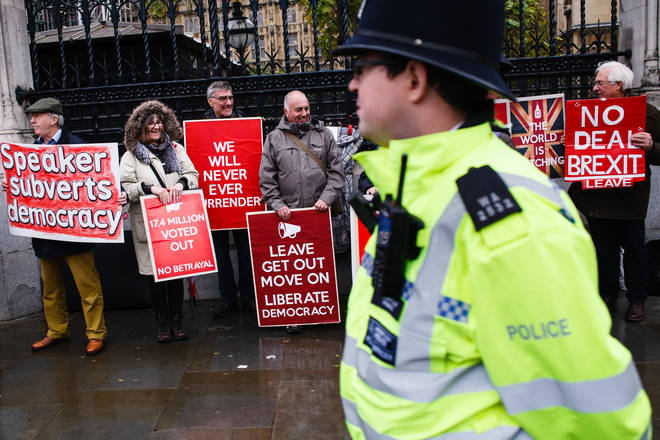 A police officer walks past pro-Brexit activists demonstrating outside the Houses of Parliament