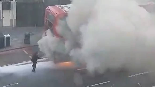 The brave passerby tries to put out the fire on the double-decker bus. Picture: Newsflare/Alex Hoods