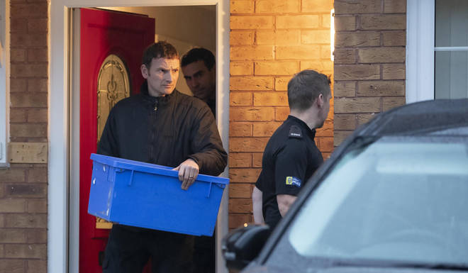 Police leave the home of a couple, both 38, with an evidence box at Wiltshire close in Warrington, Cheshire, after they were arrested on suspicion of manslaughter and conspiracy to traffic people