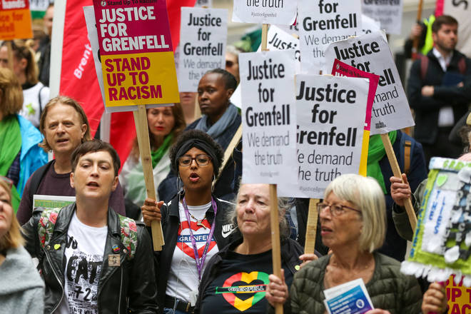 Campaigners hold placards as they take part during the Justice for Grenfell Solidarity rally this June