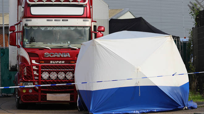 Police at the scene where 39 bodies were found in the back of a lorry