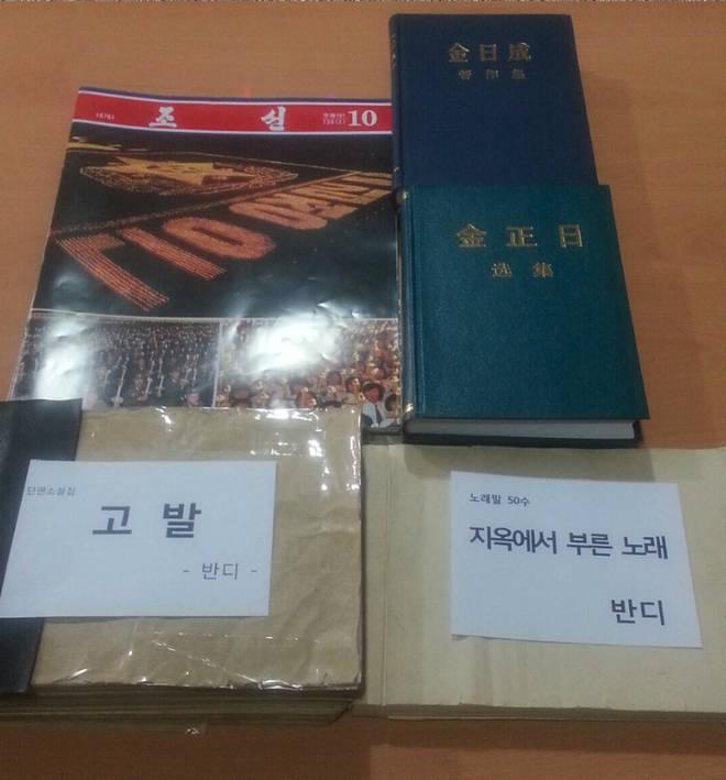 The manuscript (bottom) was smuggled by hiding it inside North Korean propaganda