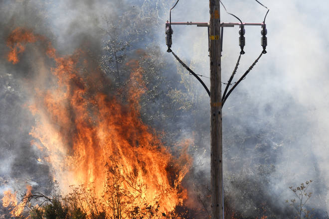 Flames erupt in the tall brush surrounding an electrical pole on a hillside in California