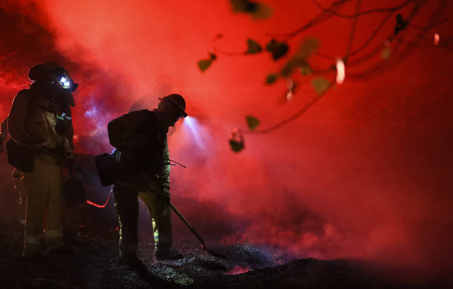 Firefighters work at a fire spot in Santa Clarita, the U.S. state of California