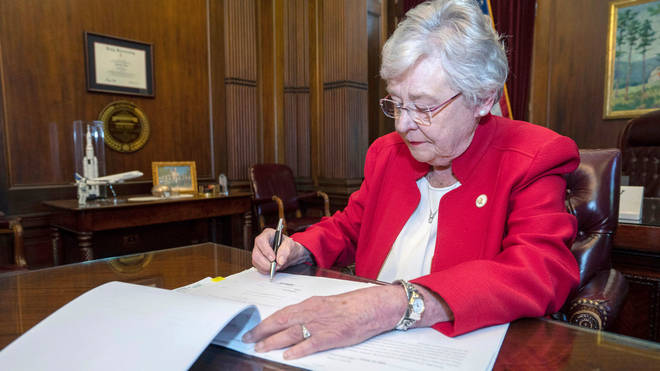 Alabama Governor Kay Ivey signing the bill to virtually outlaw abortion in the state