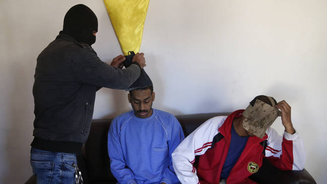 A Kurdish security officer takes off face masks from Alexanda Amon Kotey, left, and El Shafee Elsheikh