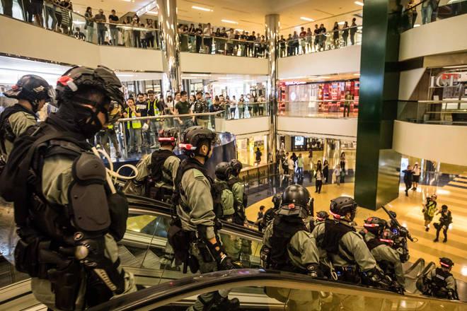 Riot police descend an escalator inside the City Plaza shopping centre in Hong Kong